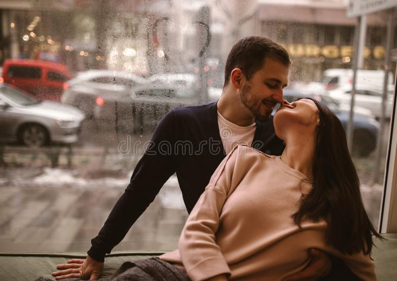 Romantisch paar Het houden van van kerel kust zijn mooie meisjezitting op de vensterbank in een comfortabele koffie royalty-vrije stock afbeeldingen