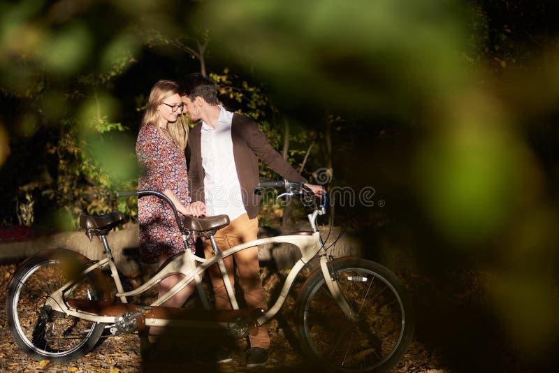 Romantisch paar, mens en aantrekkelijk meisje dicht bij elkaar bij fiets achter elkaar in donker de herfstpark stock foto