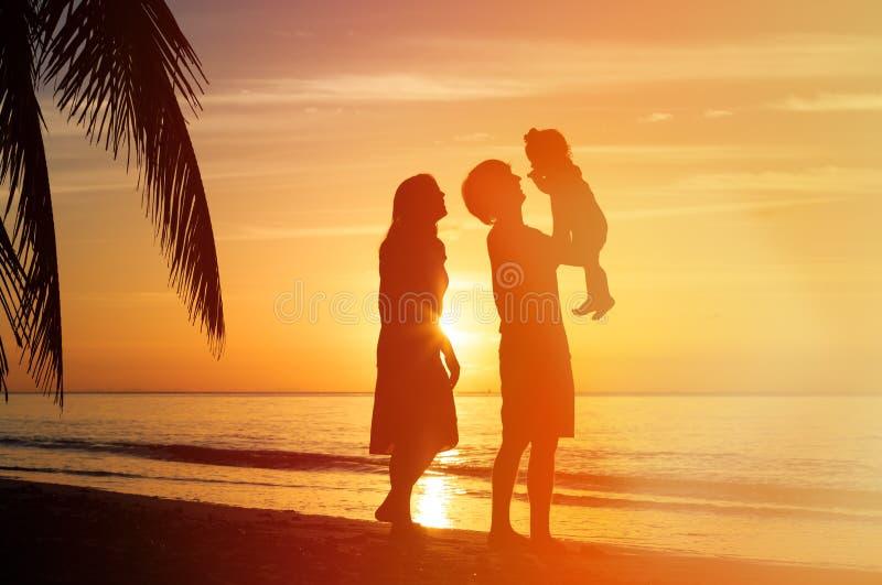 Romantisch paar met weinig kind bij zonsondergangstrand stock foto's