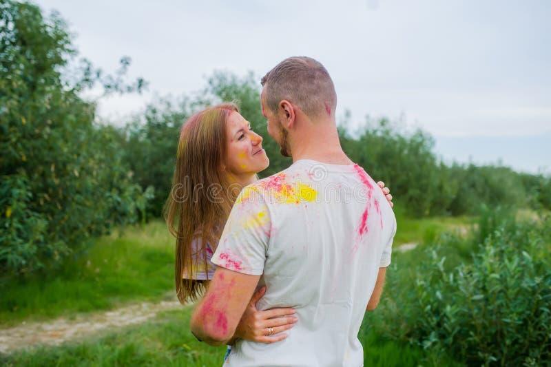 Romantisch paar in multi-colored verven die in de zomerweide koesteren stock afbeelding