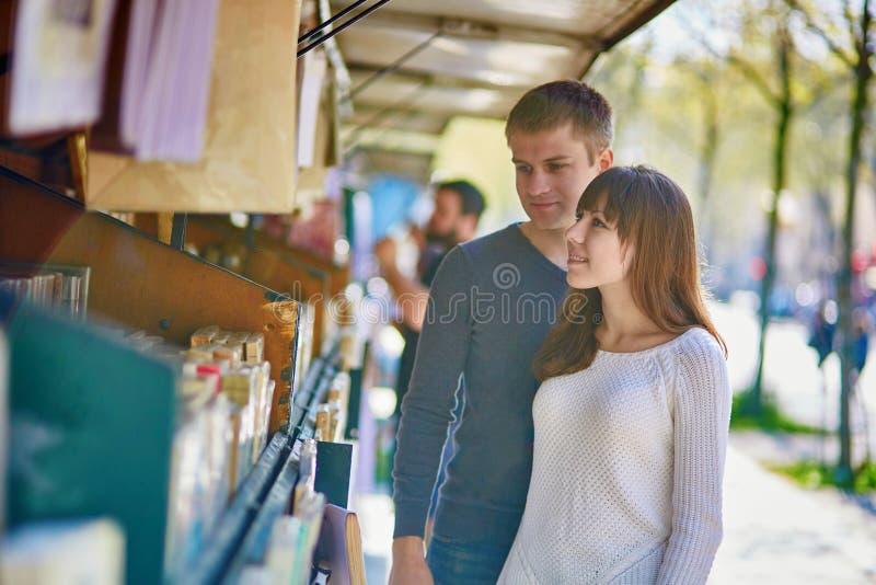 Romantisch paar in Parijs die een boek van een boekhandelaar selecteren stock afbeeldingen
