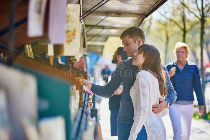 Romantisch paar in Parijs die een boek van een boekhandelaar selecteren stock afbeelding