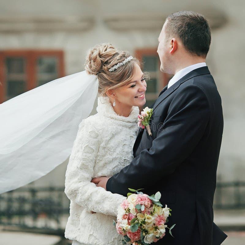 Romantisch paar van jonggehuwden die dichtbij oude kerk in de herfst koesteren stock afbeelding