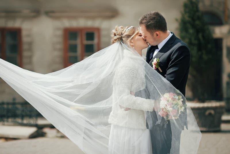 Romantisch paar van jonggehuwden die dichtbij oude kerk in de herfst kussen royalty-vrije stock foto's