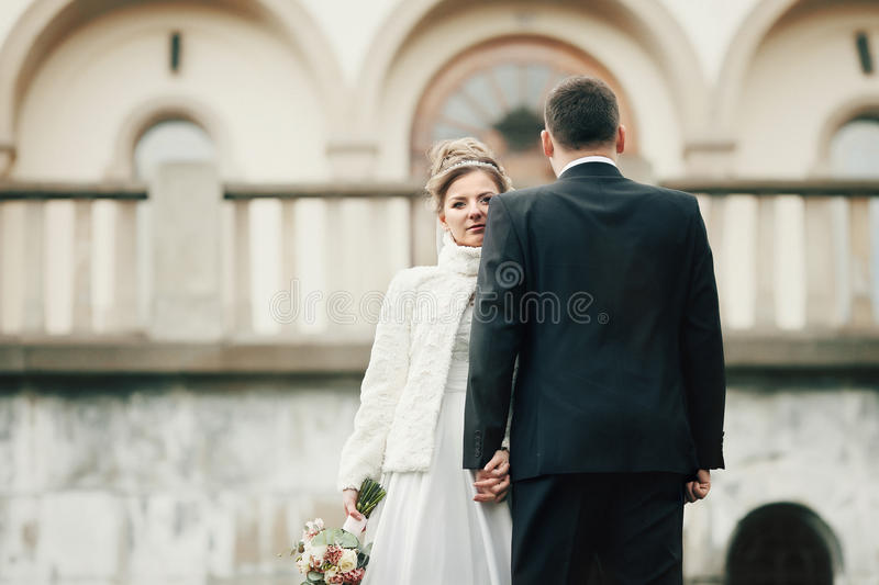 Romantisch paar van jonggehuwden die dichtbij oude kerk in de herfst stellen stock foto's