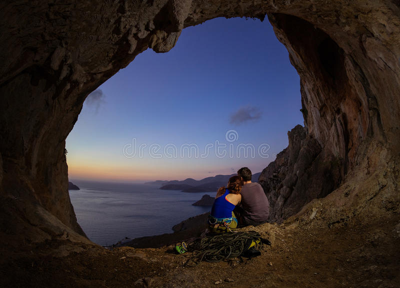 Romantisch paar van rotsklimmers die op zonsondergang van hol in cl letten stock fotografie