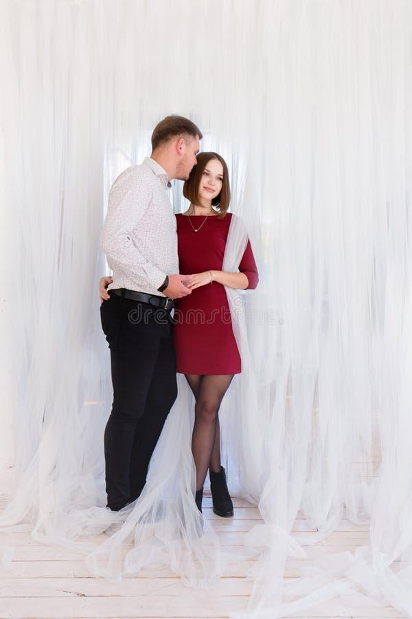 Romantisch paar in witte gordijnen stock foto