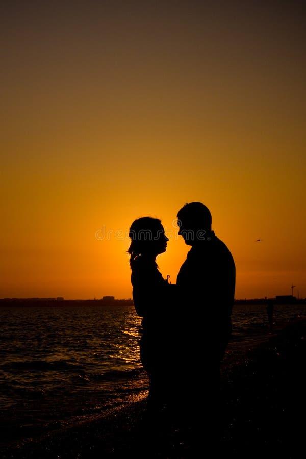 Romantisch paarsilhouet op het strand stock afbeeldingen