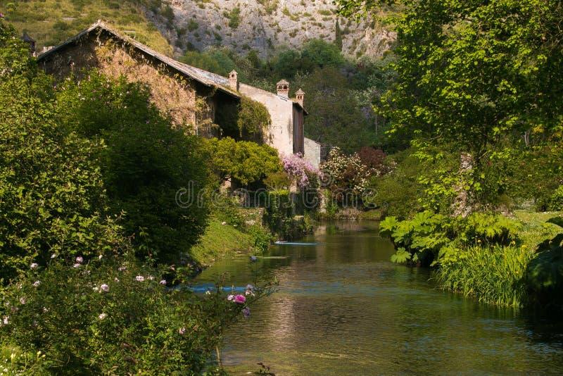 Romantisch plattelandshuisje dichtbij de rivier met bloemen royalty-vrije stock afbeeldingen