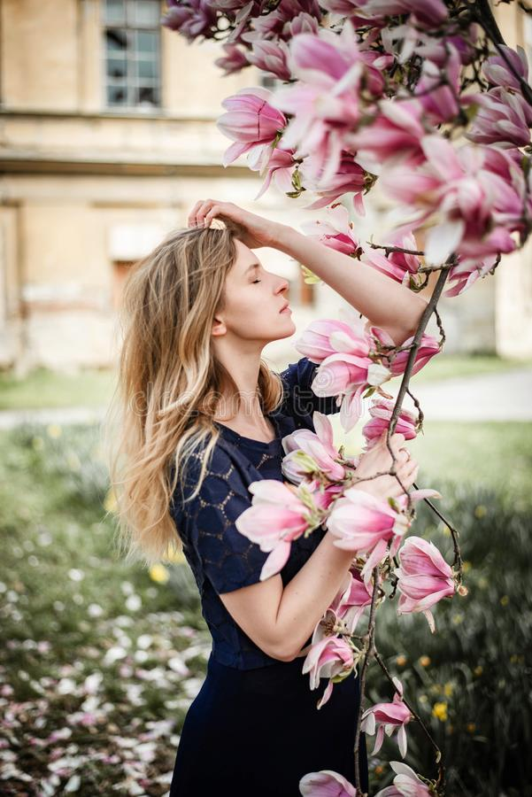Romantisch portret van het jonge blondevrouw stellen met magnoliaboom in volledige bloei stock foto's