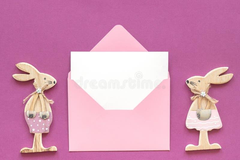 Romantisch samenstellingspaar van de houten konijnen van het minnaarsbeeldje en roze envelop met lege kaart op purper Concept als stock foto