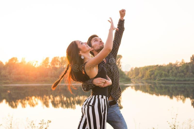 Romantisch, sociaal dans en mensenconcept - jong paar die een tango of een bachata dichtbij het meer dansen stock foto's