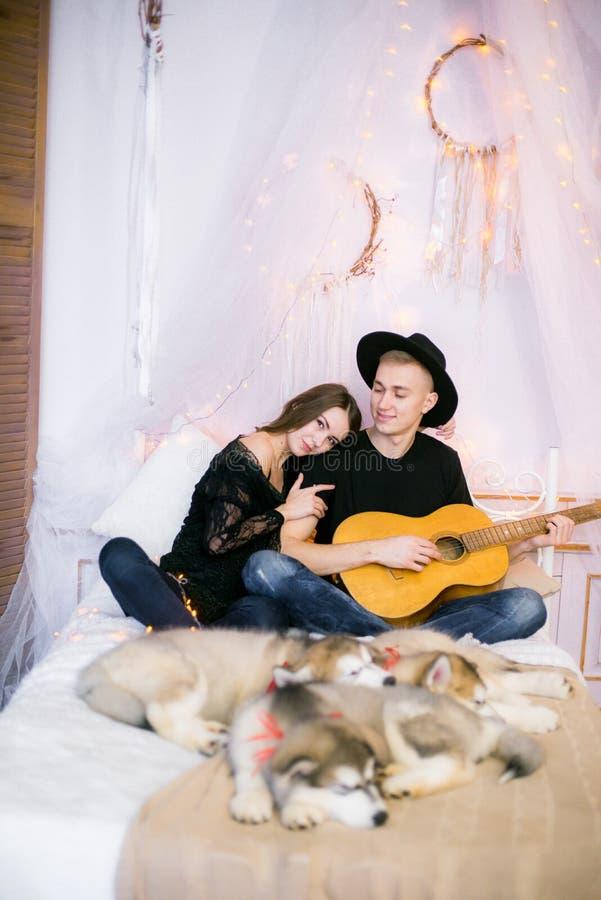Romantisch Vrolijk paar die thuis het spelen gitaar rusten mens het spelen gitaar voor zijn geliefd meisje stock foto