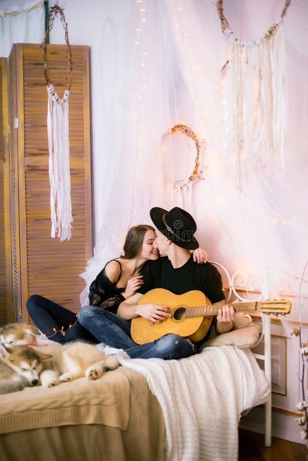 Romantisch Vrolijk paar die thuis het spelen gitaar rusten mens het spelen gitaar voor zijn geliefd meisje royalty-vrije stock afbeelding