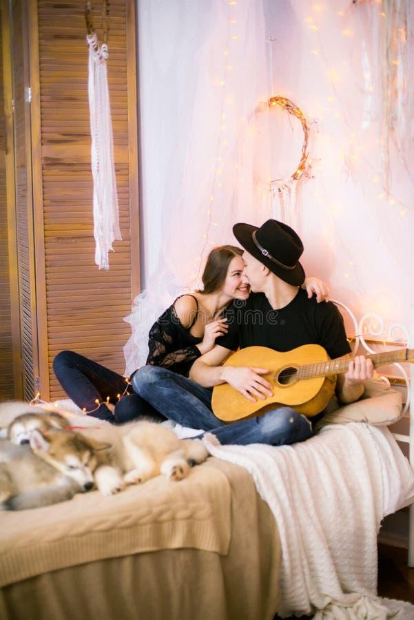 Romantisch Vrolijk paar die thuis het spelen gitaar rusten mens het spelen gitaar voor zijn geliefd meisje royalty-vrije stock afbeeldingen