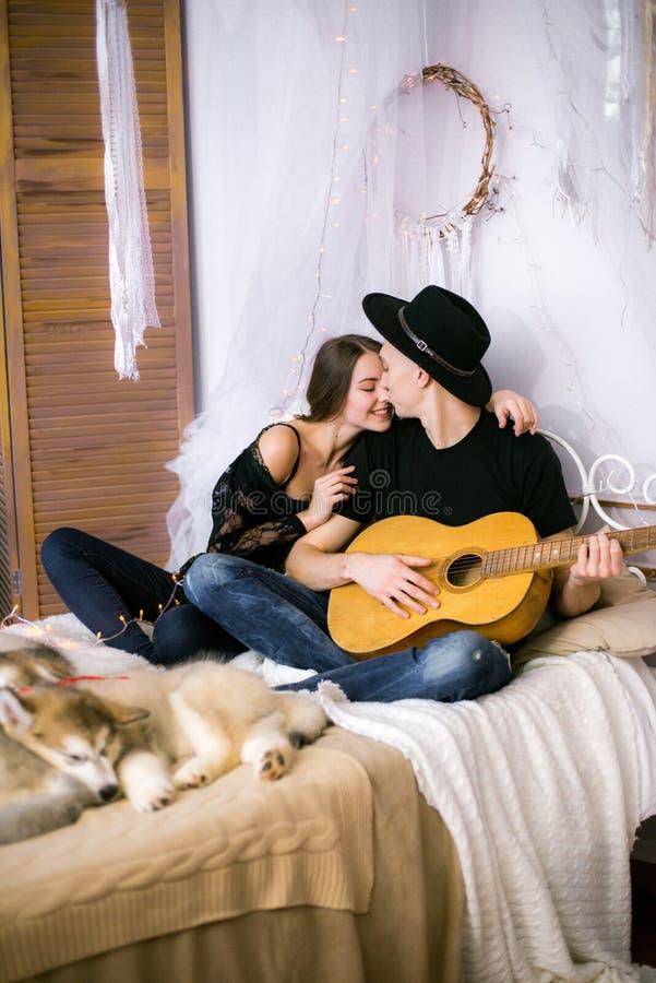 Romantisch Vrolijk paar die thuis het spelen gitaar rusten mens het spelen gitaar voor zijn geliefd meisje royalty-vrije stock foto