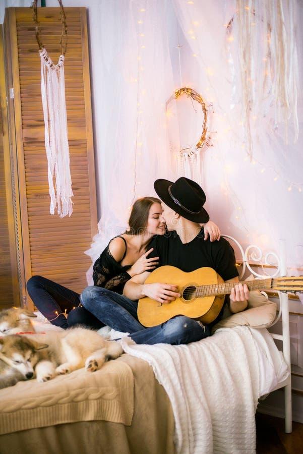 Romantisch Vrolijk paar die thuis het spelen gitaar rusten mens het spelen gitaar voor zijn geliefd meisje royalty-vrije stock fotografie