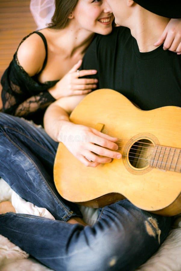 Romantisch Vrolijk paar die thuis het spelen gitaar rusten mens het spelen gitaar voor zijn geliefd meisje stock fotografie