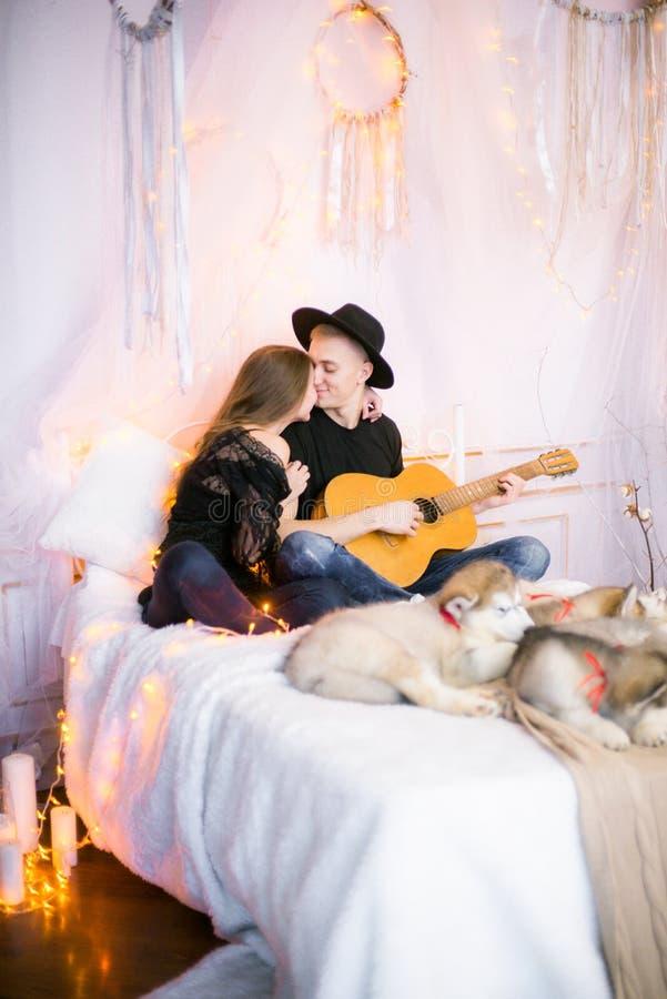 Romantisch Vrolijk paar die thuis het spelen gitaar rusten mens het spelen gitaar voor zijn geliefd meisje stock foto's