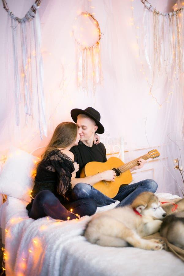 Romantisch Vrolijk paar die thuis het spelen gitaar rusten mens het spelen gitaar voor zijn geliefd meisje royalty-vrije stock foto's
