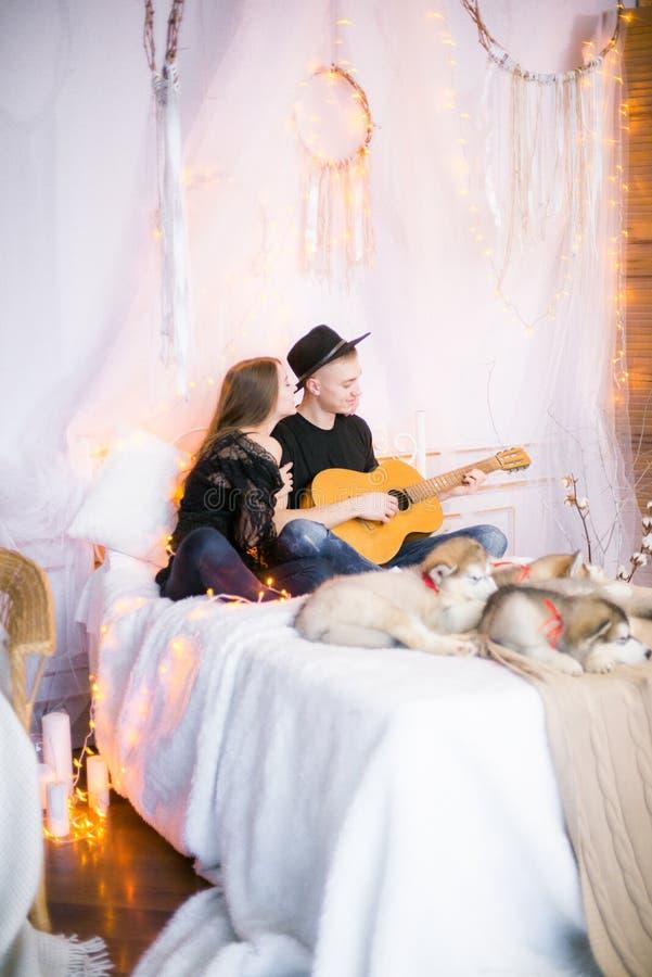 Romantisch Vrolijk paar die thuis het spelen gitaar rusten mens het spelen gitaar voor zijn geliefd meisje stock afbeeldingen