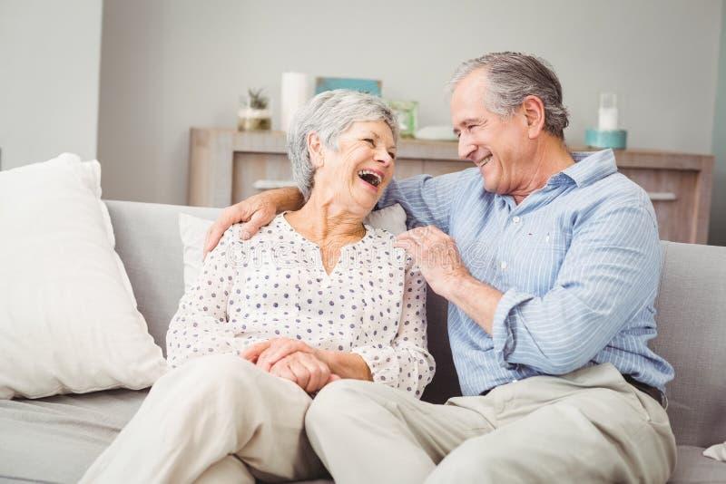 Romantische ältere lachende Paare beim Sitzen auf Sofa lizenzfreies stockbild