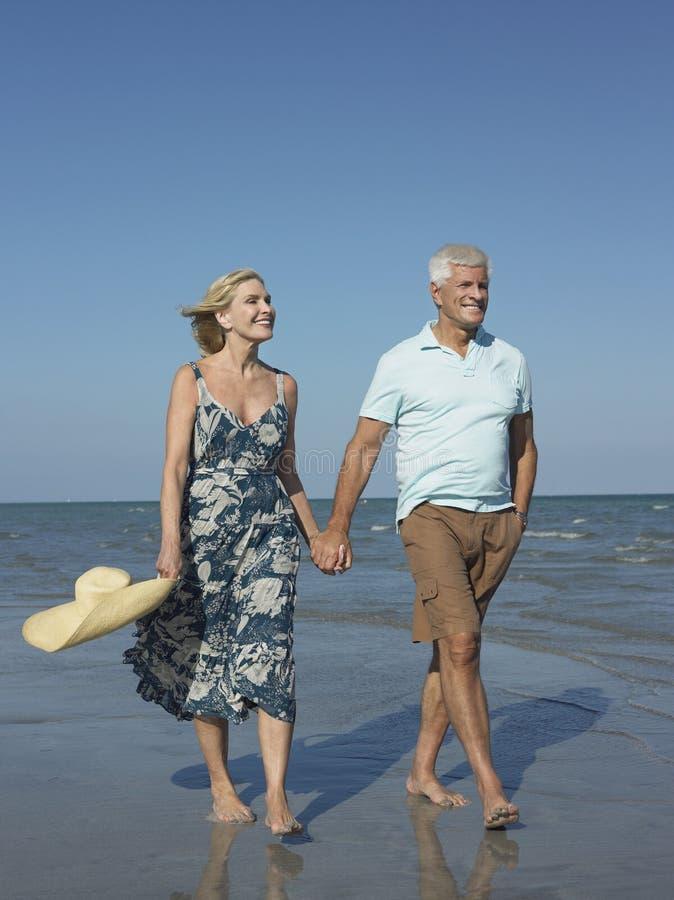 Romantische ältere Paare, die auf Strand gehen lizenzfreies stockfoto