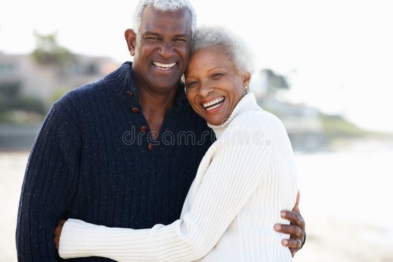 Romantische ältere Paare, die auf Strand umarmen stockfotografie