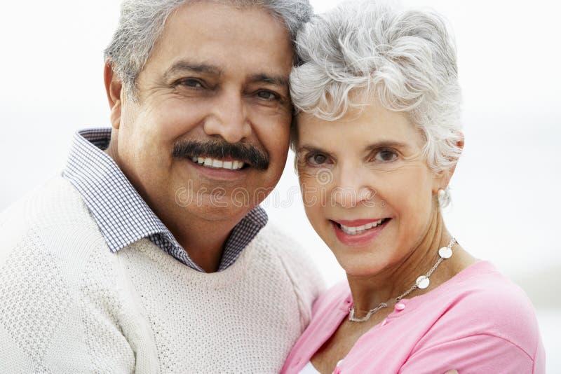 Romantische ältere Paare, die auf Strand umarmen stockbilder