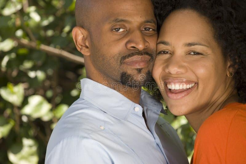 Romantische Afroamerikanerpaare, die draußen umarmen lizenzfreies stockbild