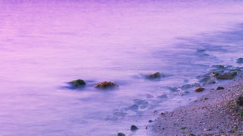 Romantische atmosfeer in vreedzame ochtend op zee Grote keien die uit van vlotte golvende overzees plakken stock fotografie