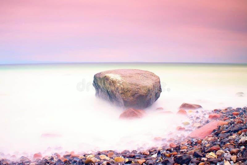 Romantische atmosfeer in vreedzame ochtend op zee Grote keien die uit van vlotte golvende overzees plakken Roze Horizon royalty-vrije stock afbeelding