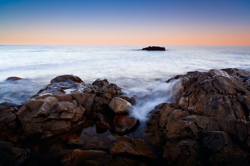 Romantische atmosfeer in vreedzame ochtend op zee Grote keien die uit van vlotte golvende overzeese Roze horizon met eerste heet  stock foto