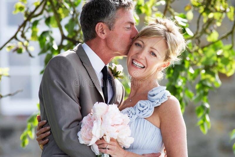 Romantische Braut und Bräutigam Embracing Outdoors stockfoto