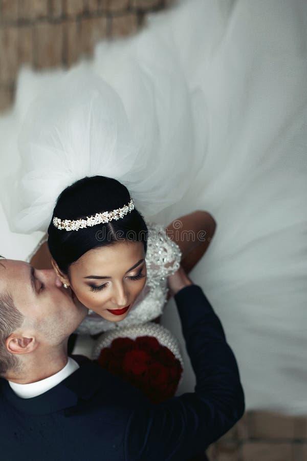 Romantische bruidegom die donkerbruine bruid op de hals, schot van abo kussen stock foto