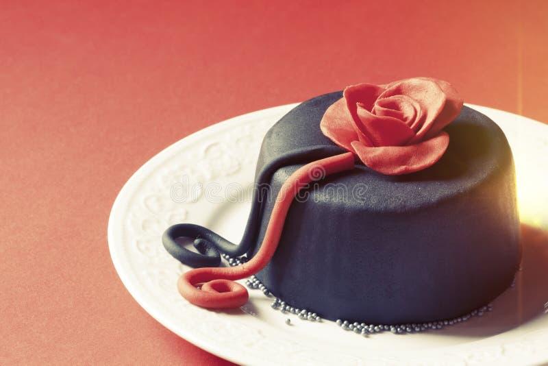 Romantische cake op een plaat met decoratie Nam hierboven toe Schaduwen rode achtergrond royalty-vrije stock afbeelding