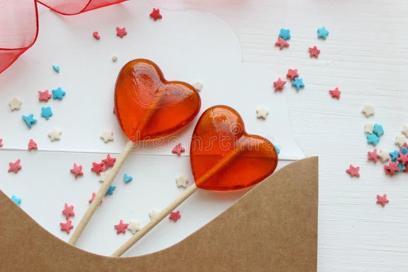 Romantische de Dagachtergrond van Valentine ` s De daggift van Valentine ` s Prentbriefkaar en twee lollys in de vorm van rode ha stock foto's