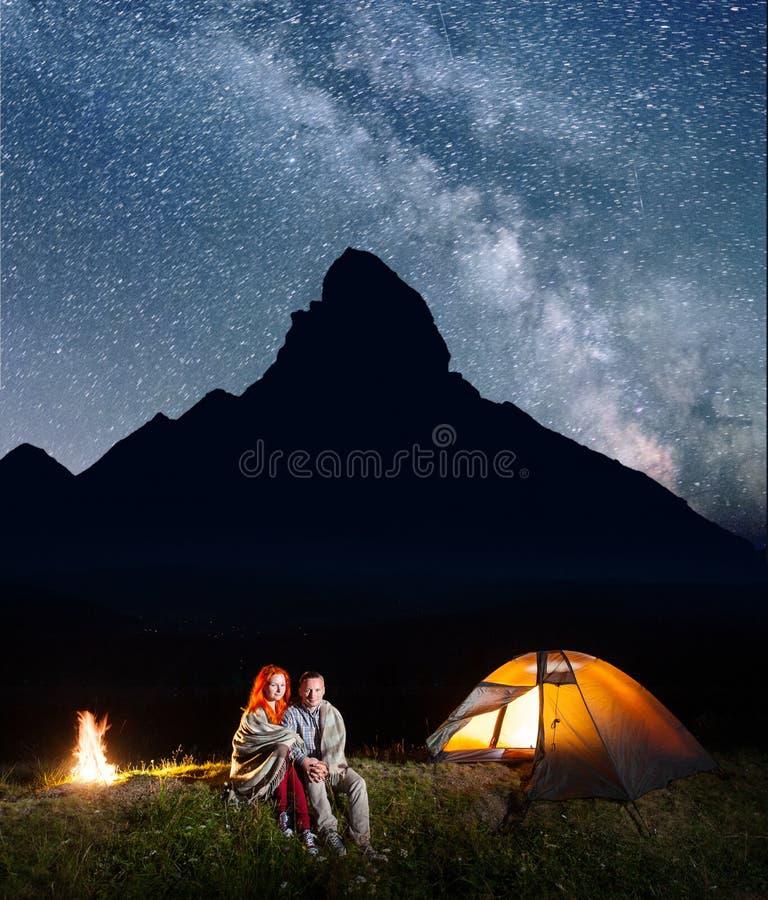 Romantische Familientouristen bedeckt mit einem Plaid, das zusammen nahe Lagerfeuer und Glanzzelt nachts sitzt stockfotos
