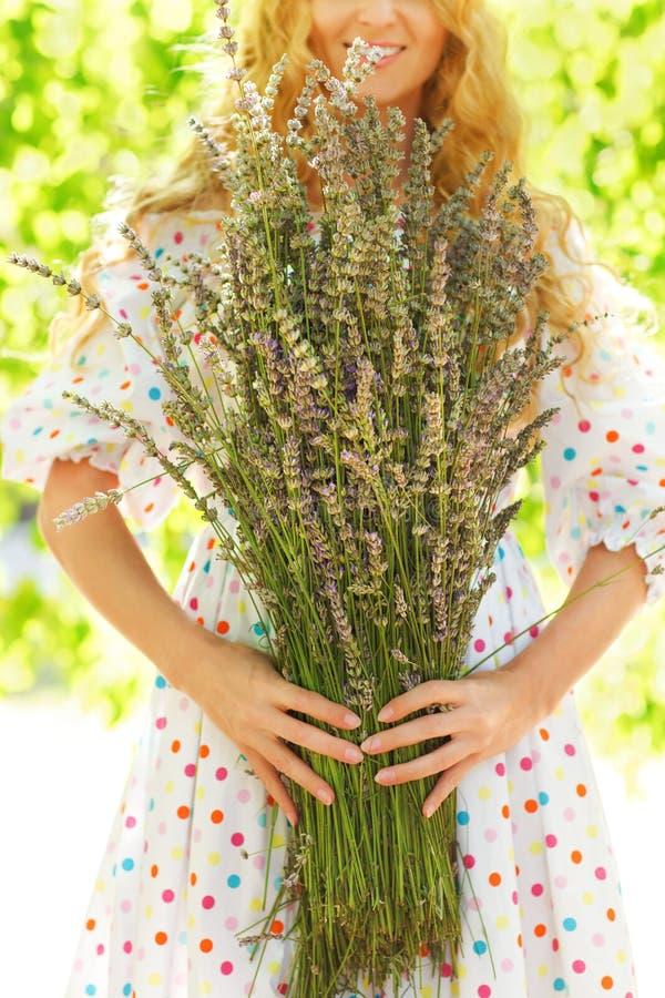 Romantische Frau mit dem langen blonden Haar mit Lavendelblumenstrauß lizenzfreies stockfoto