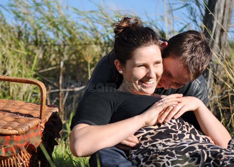 Romantische Frau u. Mann, die draußen Picknick coun genießen lizenzfreie stockfotografie