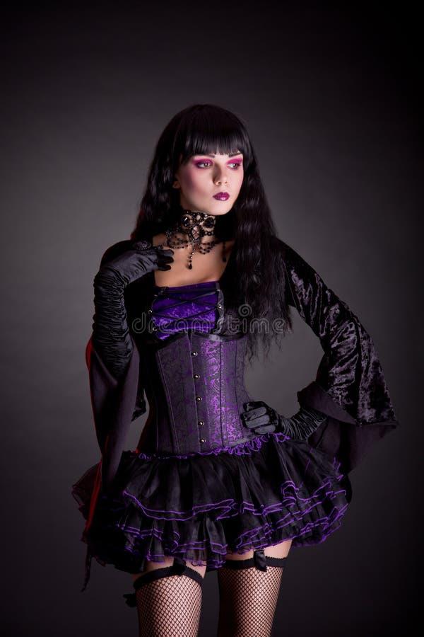 Romantische heks in purpere en zwarte gotische Halloween-uitrusting royalty-vrije stock fotografie