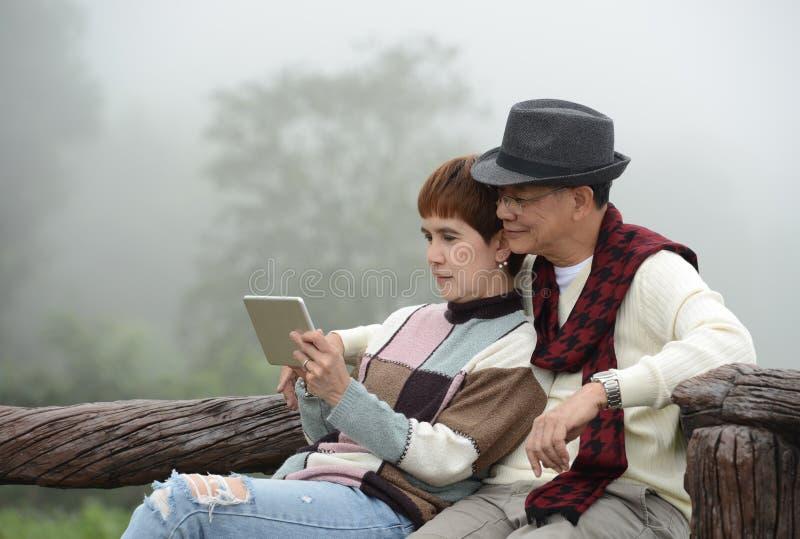 Romantische hogere paren die digitale tablet gebruiken stock foto