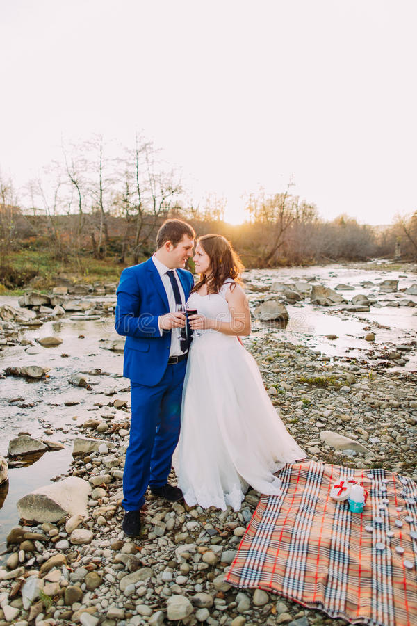 Romantische jonge jonggehuwdepaar het drinken wijn op de rotsachtige bank van de kiezelsteenrivier met bosheuvels en stroom stock foto