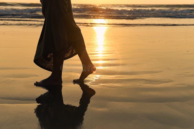 Romantische jonge meisjesgangen op het strand blootvoets in het water Vrouwenwandeling blootvoets in het overzees bij zonsonderga royalty-vrije stock foto