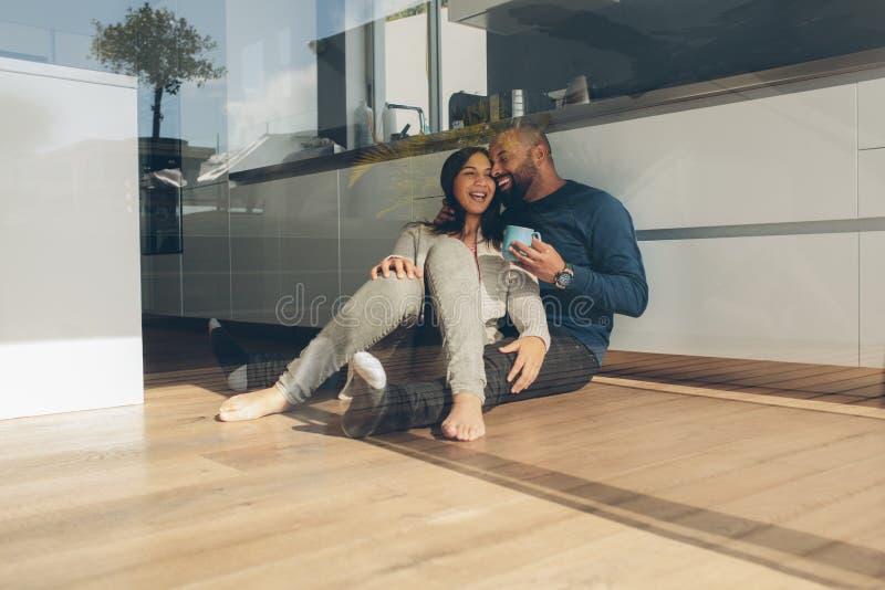 Romantische jonge paarzitting op keukenvloer in ochtend royalty-vrije stock foto