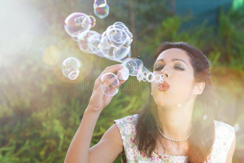 Romantische jonge vrouw die kleurrijke zeep opblaast royalty-vrije stock foto's