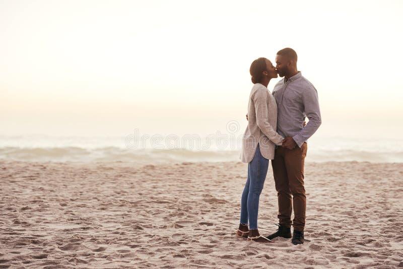 Romantische junge afrikanische Paare, die auf einem Strand an der Dämmerung küssen stockbilder