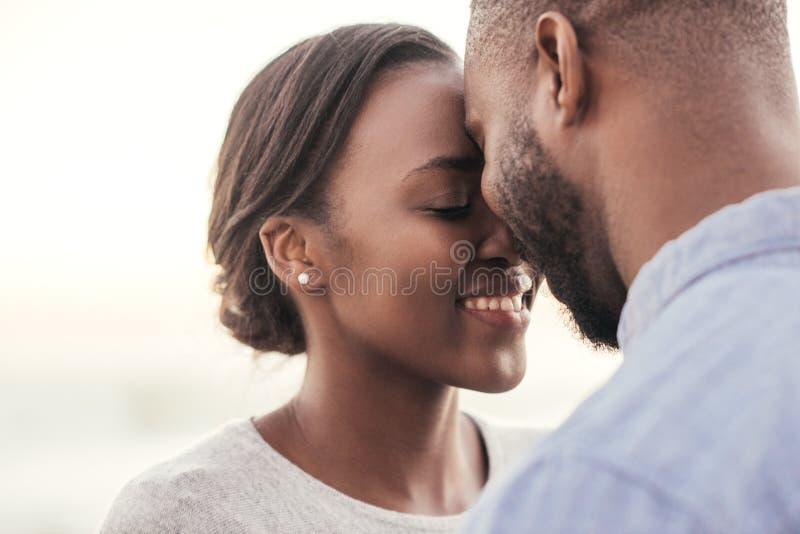 Romantische junge afrikanische Paare, die zusammen Moment am Strand genießen stockfotos
