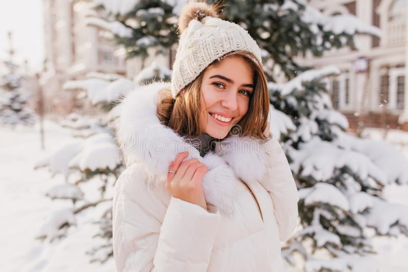 Romantische junge Frau in der modischen Strickmütze, die mit Lächelnstellung nahe Weihnachtsschneebedecktem Baum aufwirft Foto im lizenzfreie stockfotografie