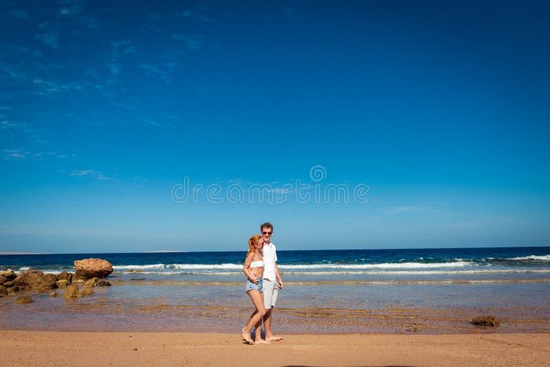 Romantische junge Paare auf dem Strand stockfotos